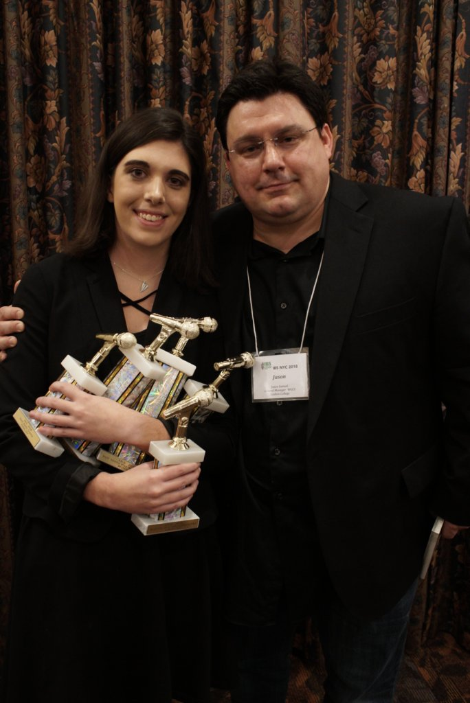 Male professor with female student holding 5 trophies