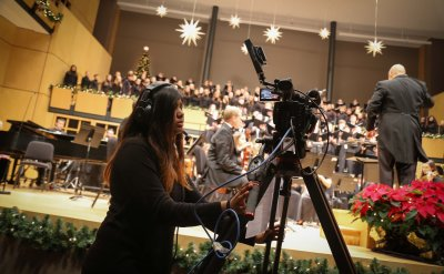 A female student recording a Choirs and Orchestra during a music performance