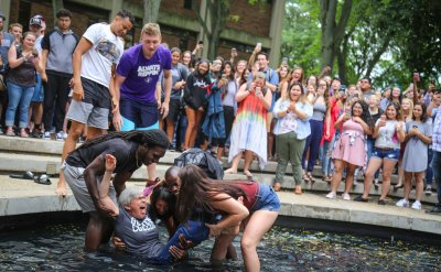 Four students dunk President Becky in the fountain surrounded by the student body