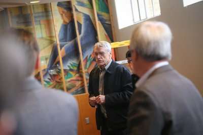 Man speaking to a group in front of a painting