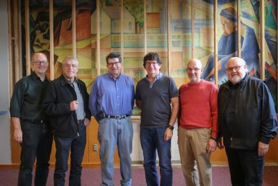 Six men standing in front of a painting