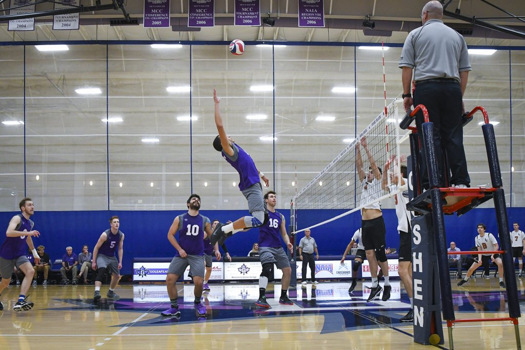 Man from Goshen's volleyball team reaching for the volleyball in the air, ready to spike it across the net.