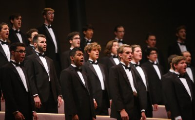 Mens Choir standing while singing in Sauder Concert Hall.