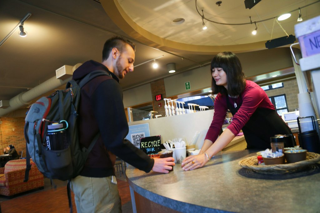 A student giving and a student receiving iced coffee at Java Junction.