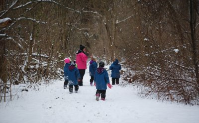 Kindergarten Teacher and students walking in the forest during the winter with snow all around them.