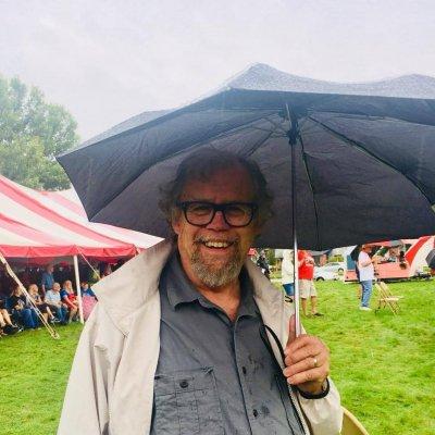 Allen under an umbrella, smiling
