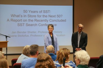 "A woman and man in front of a projection that says ""50 Years of SST: What's in Store for the Next 50?"""