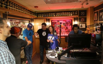 Multiple people from off campus touring the radio station while a student is working on the computer.