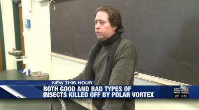 Professor standing in front of chalkboard.