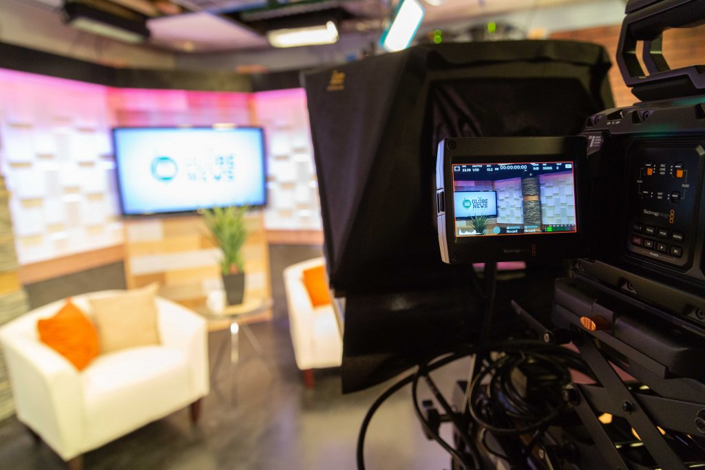 TV camera set up looking at host chairs and background TV.