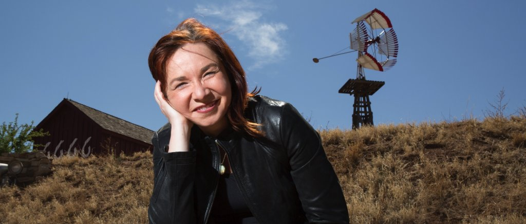 Woman with grassy hill and wind machine in the background