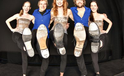 Three women and two men holding up their tap shoes in a line with their arms around each other with one foot in the air