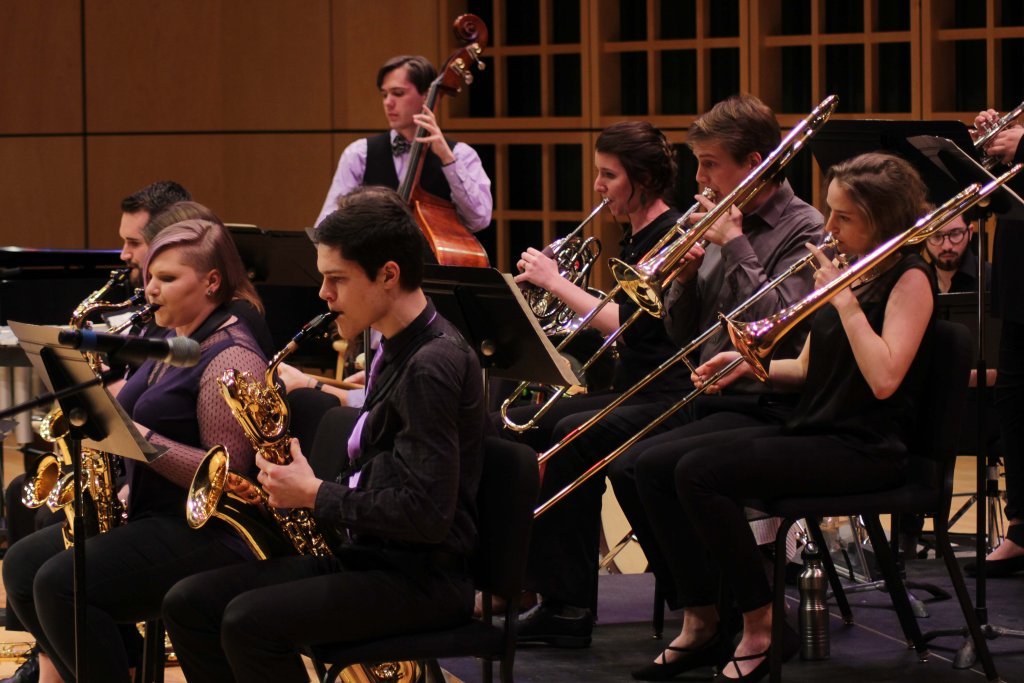 Jazz ensemble featuring people playing saxophones, trombones, french horn and upright bass
