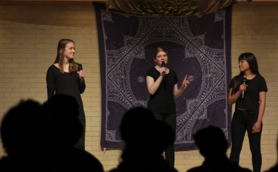 Three women dressed in black on stage with a patterned cloth behind them