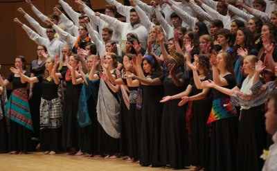 Men's choir, dressed in white shirts and holding their fists in the air, and Women's choir, dressed in black with colorful scarves, singing and clapping