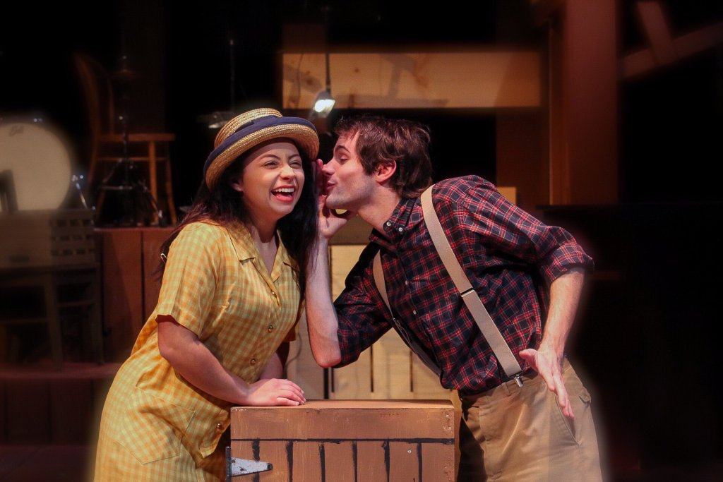 Two students playing character roles in a musical. Male is telling the female a secret while the female is laughing