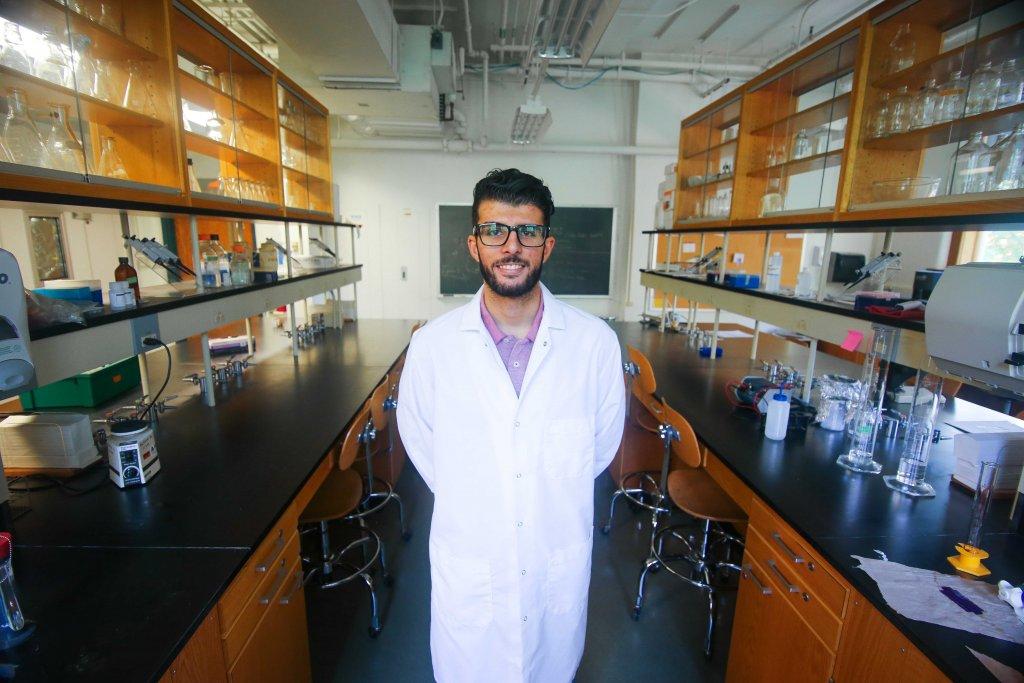 Yazan Meqbil in the chemistry lab wearing a lab coat
