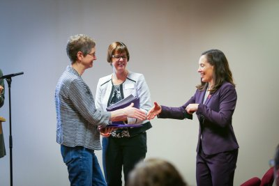 Two women shake hands while a third looks on.