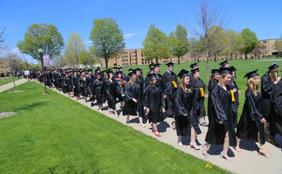 Students wearing caps and gowns walking down the sidewalk