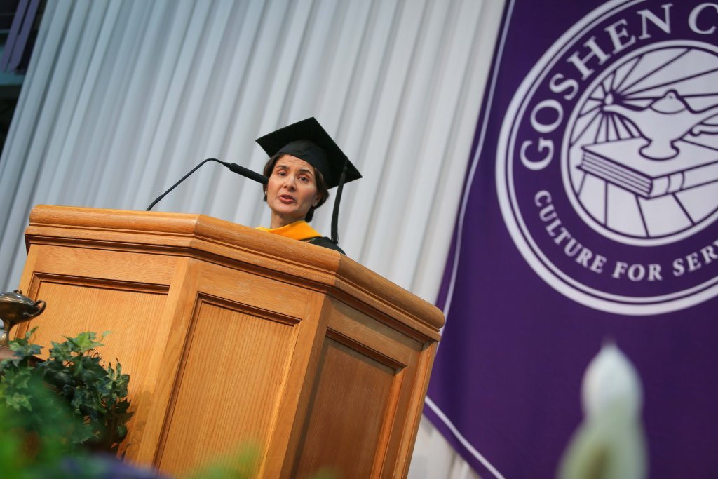 woman wearing a cap and gown giving a speech
