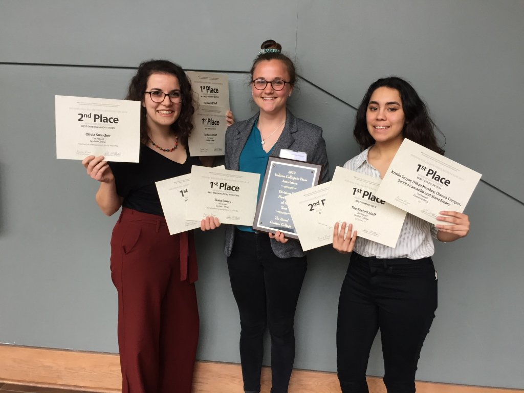 Three female students holding certificates and a plaque.