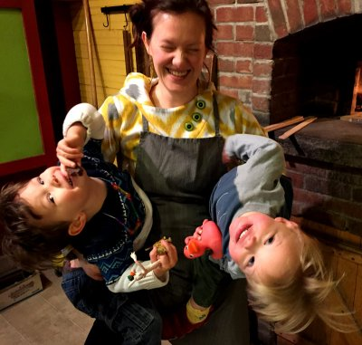 Woman wearing an apron and holding two young children in her arms