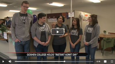 A picture of a video. A man and four women in a row wearing grey Goshen College shirts