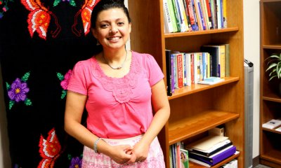 Rocio Diaz standing in front sewn flower wall hanging and next to bookshelves