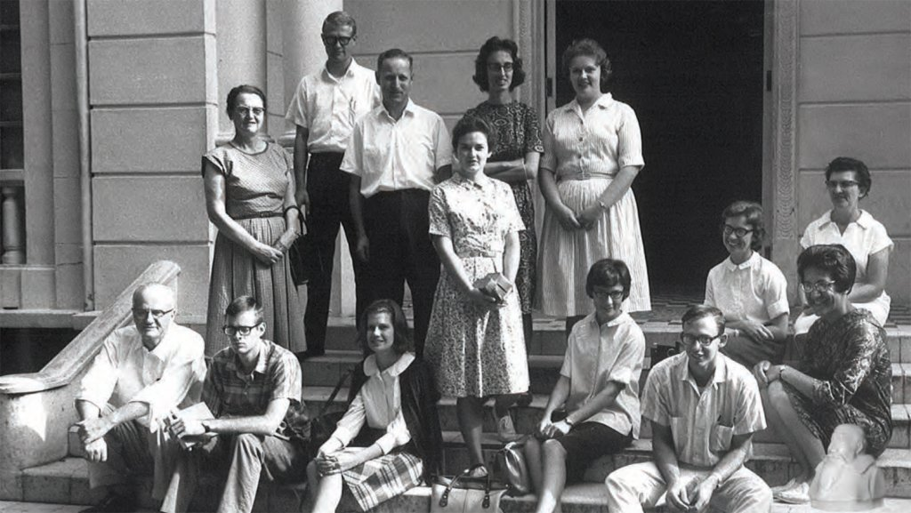 Black and white photo of fourteen people standing or sitting on steps