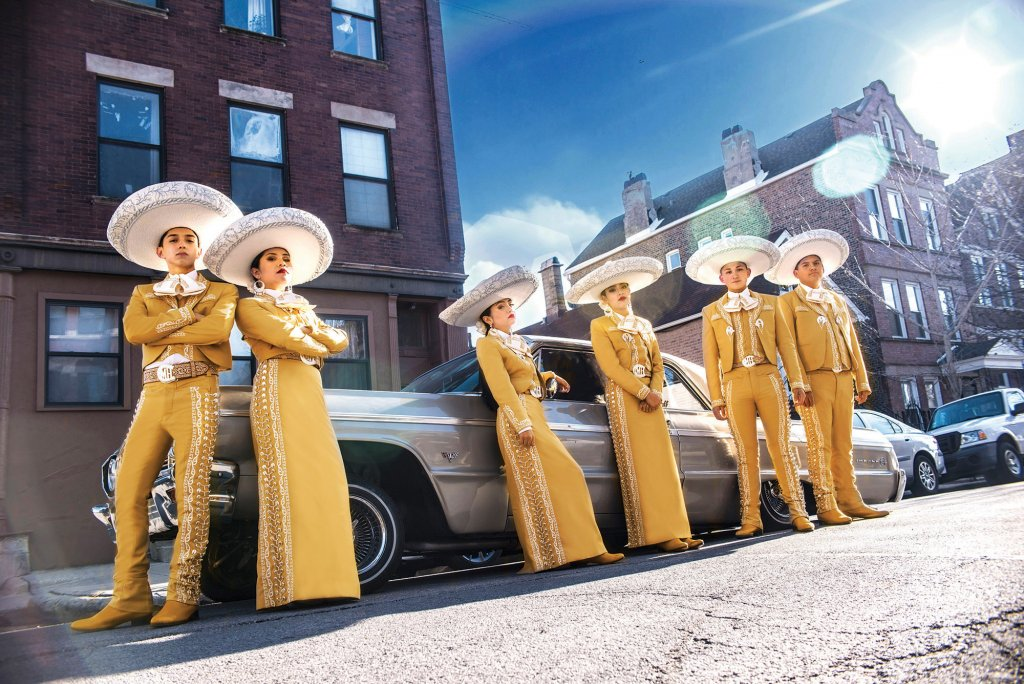 Six people in traditional Mexican attire leaning against a silver car