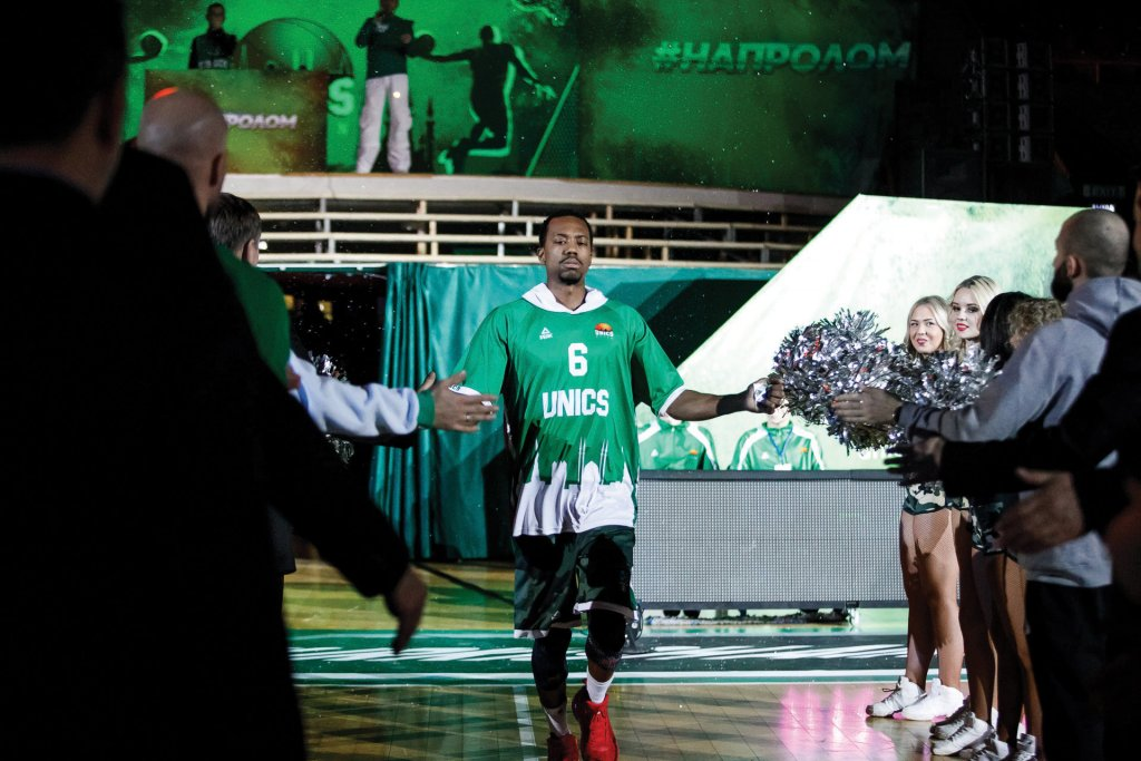 Man in a green and white basketball jersey high-fiving people