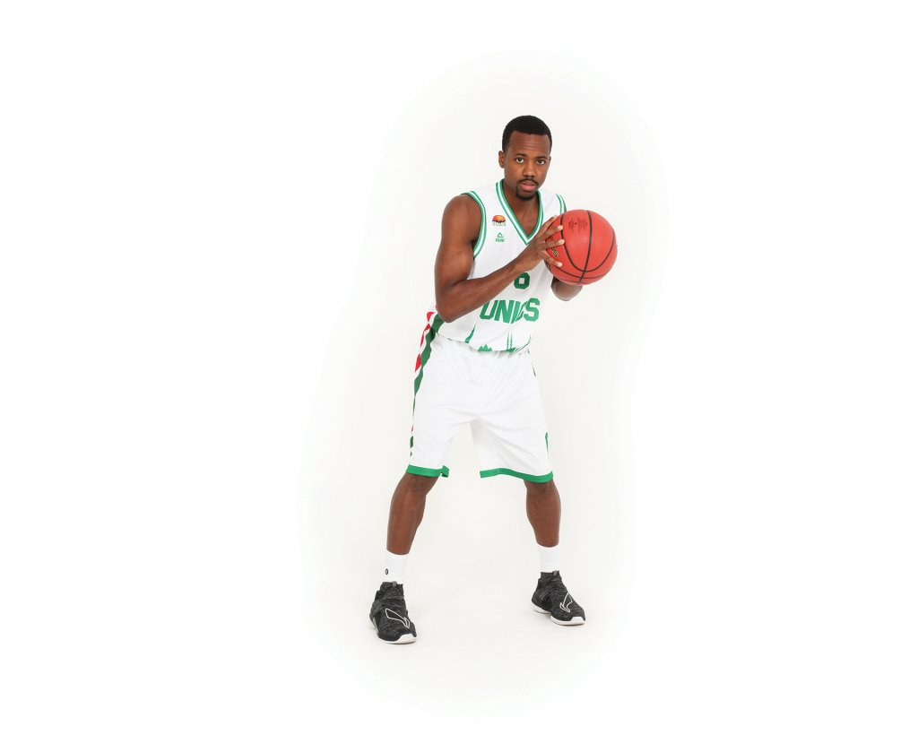 Man in a white jersey with green borders on it holding a basketball