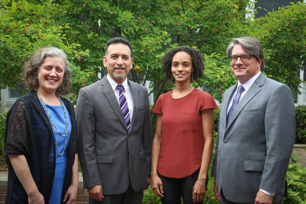 Four people standing in front of a tree. Two women and two men
