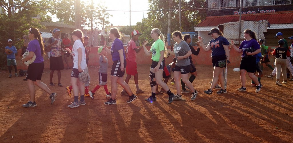 A group of people walking across a softball field