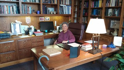 Geraldine Chan at a desk surrounded by bookshelves