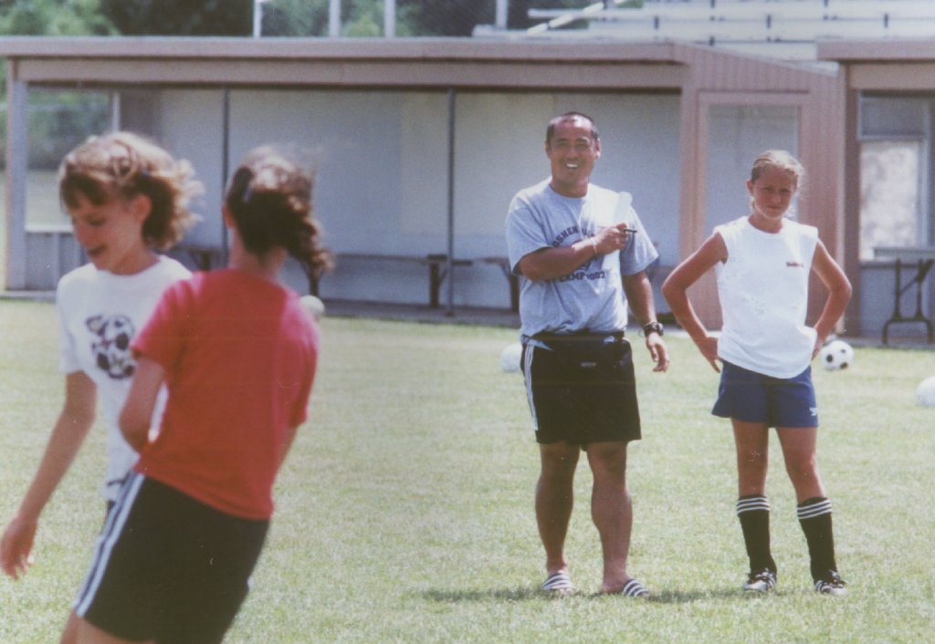 Four people on a field. One adult and three youth. They are wearing soccer uniforms with a soccer ball in the background
