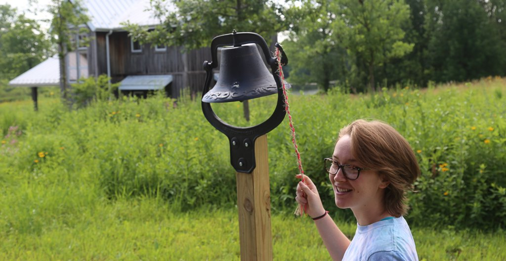Woman ringing a bell in front of a field