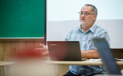 Man sitting at a desk talking with a laptop in front of him