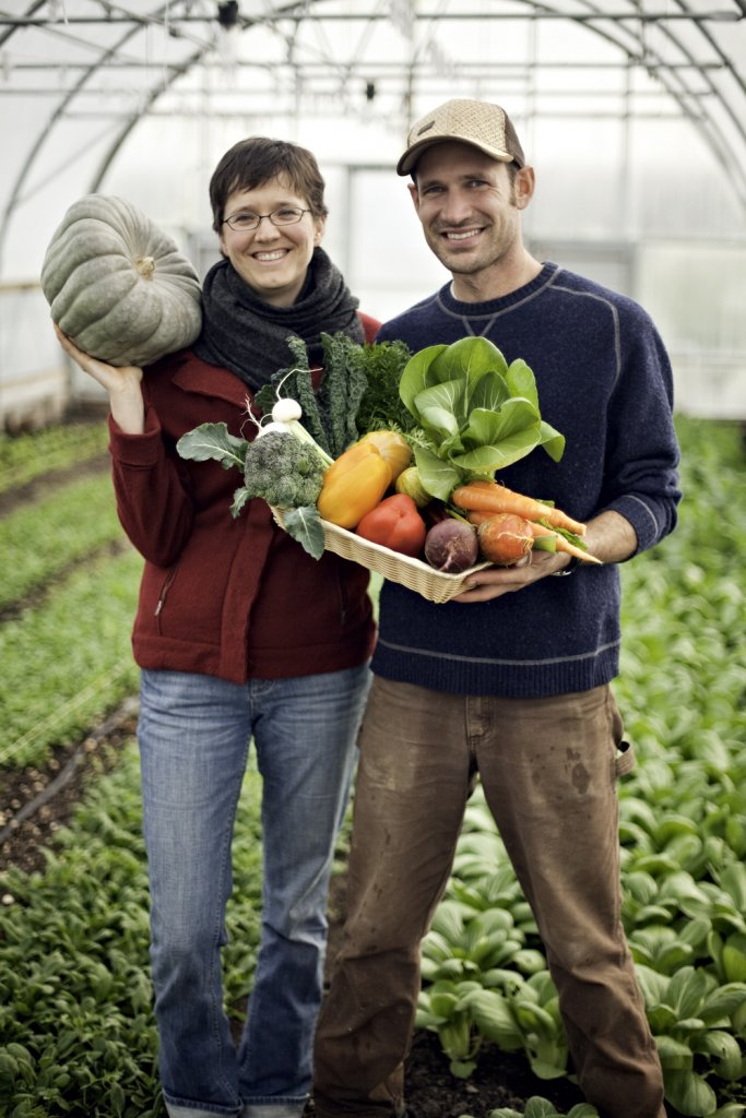 Man and a woman standing in a garden holding vegetables