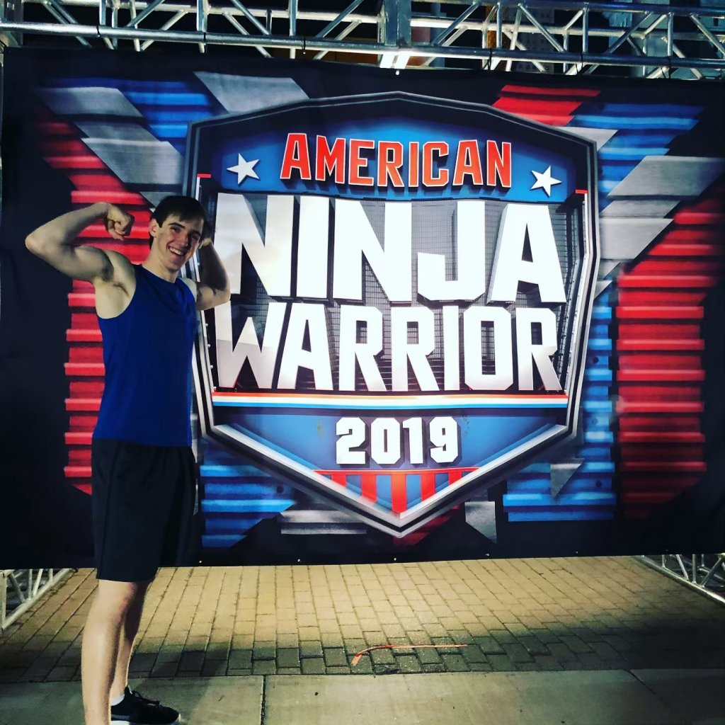 Man flexing in front of American Ninja Warrior 2019 sign