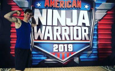 Man flexing in front of American Ninja Warrior 2019 sign