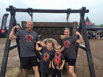 Two adults and two children flexing in front of a sign