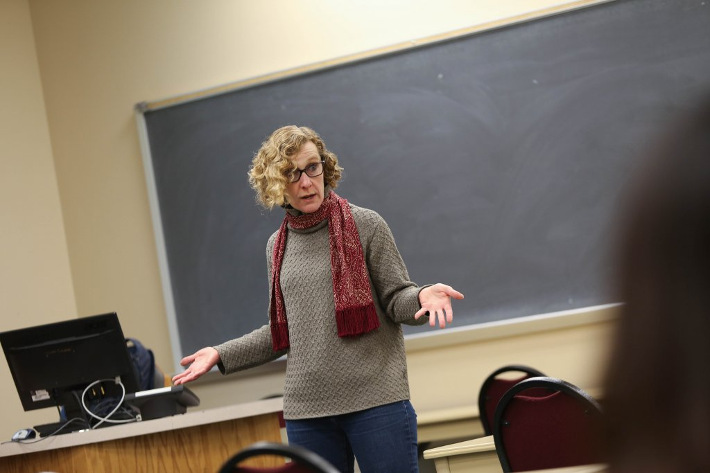 Woman standing up and teaching in front of a classroom
