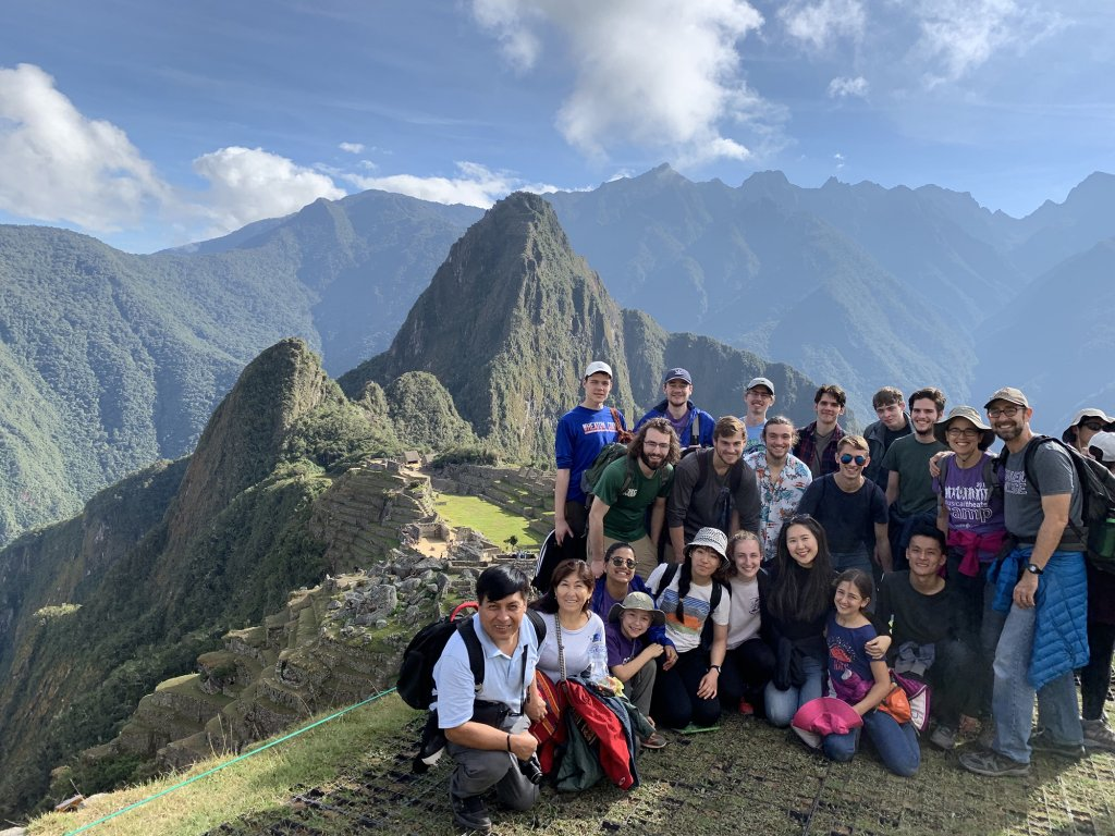 A group of people posing for a picture in front of mountains