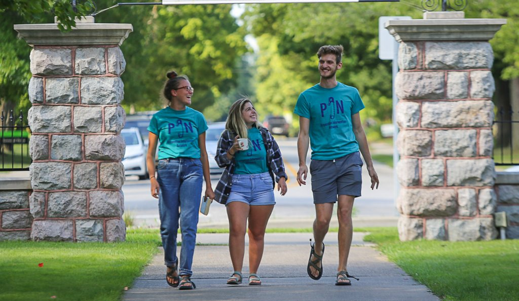Three people wearing PIN shirts in front of Goshen College entrance