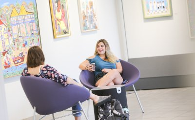 Two women sitting on purple chairs facing each other with paintings on the white walls behind them