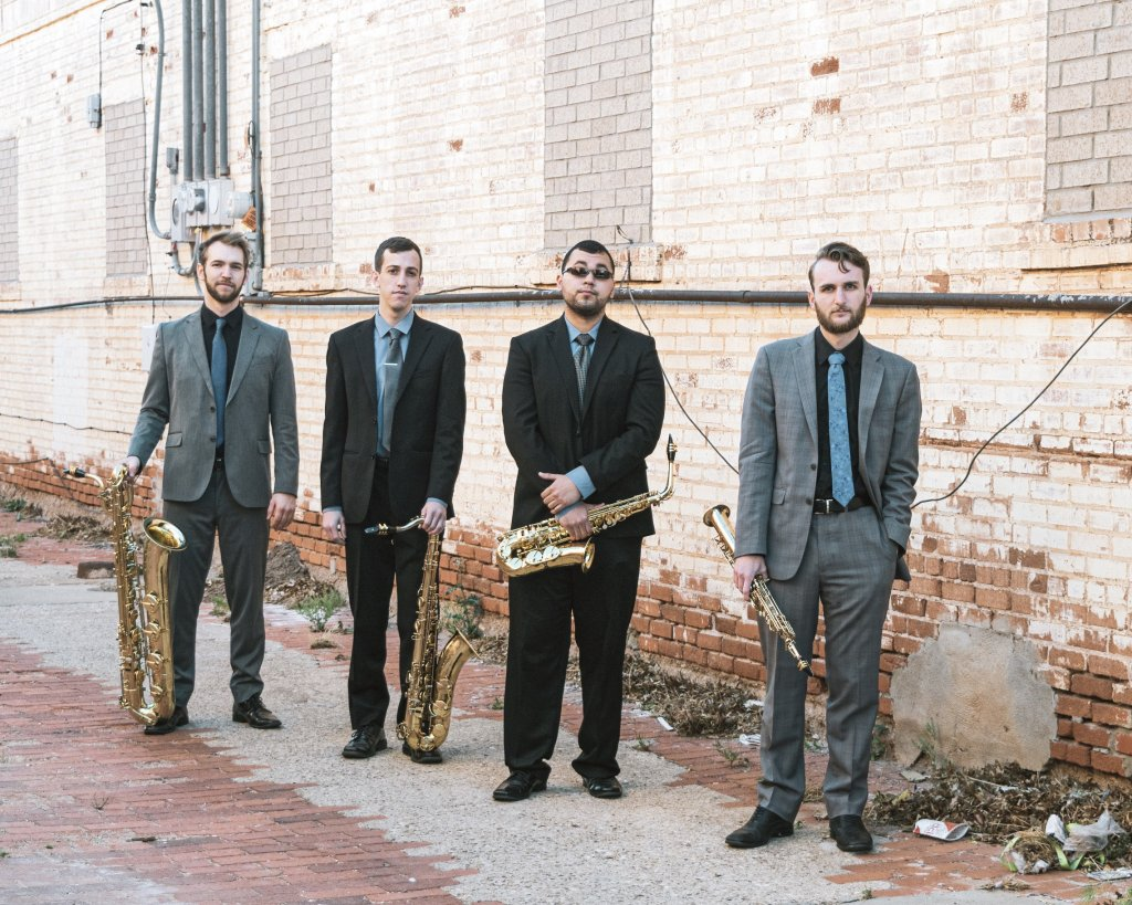 Four men in suits standing in front of a brick wall and holding brass instruments
