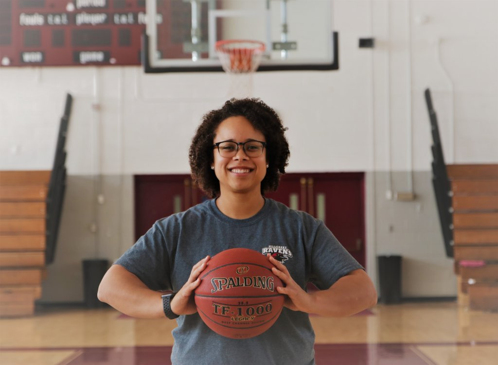 Woman in a gym holding a basketball