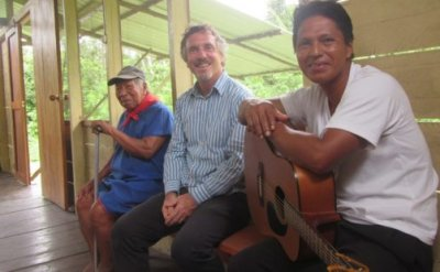 Three men sitting in a row. A man on one end is holding a cane while the man at the other end is holding a guitar