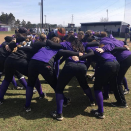 A group of athletes wearing purple and black in a huddle